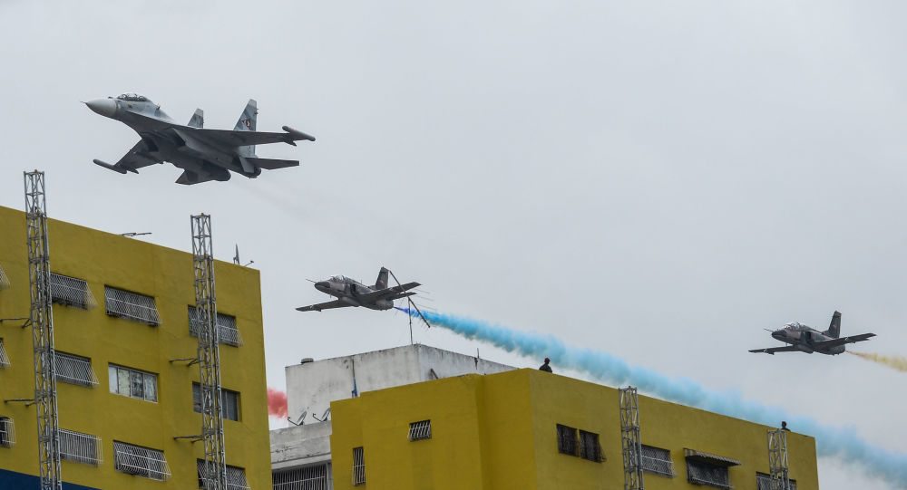 A Russian-made Venezuelan Air Force Sukhoi Su-30MKV multirole strike fighter followed by a Chinese-made Hongdu K-8 Karakorum trainer overfly the parade during the celebration of Venezuela's Independence Day in Caracas on July 5, 2015