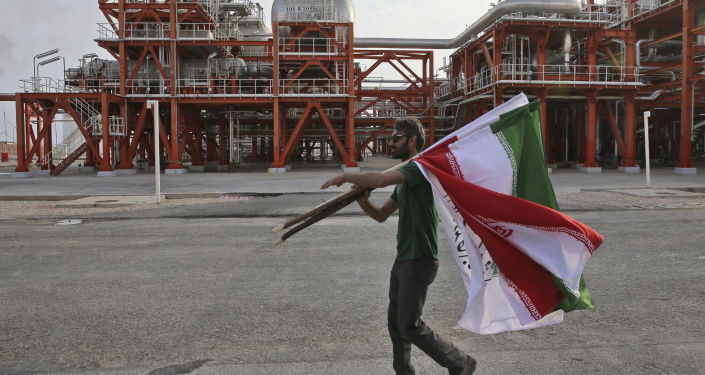 An Iranian worker carries Iranian flags prior to an inauguration ceremony of a natural gas refinery at the South Pars gas field on the northern coast of the Persian Gulf, in Asaluyeh, Iran