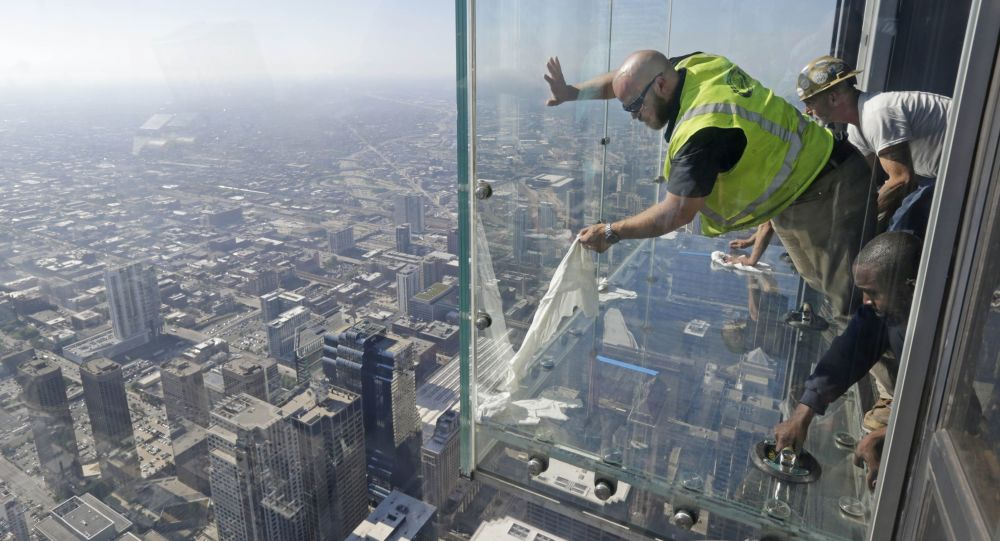 Glaziers from MTH Industries finish replacing a layer of protective coating over the glass surface on the floor of one of four transparent ledges that jut out from the 103rd floor of the Willis Tower in Chicago on Thursday, May 29, 2014. The see-through glass bays known as The Ledge were designed with a protective coating that completely covers all glass surfaces to protect against scratches. One of the coatings cracked Wednesday night when a family was standing on it. Officials say the family wasn't in danger and the coating does not affect the structural integrity of the enclosure.