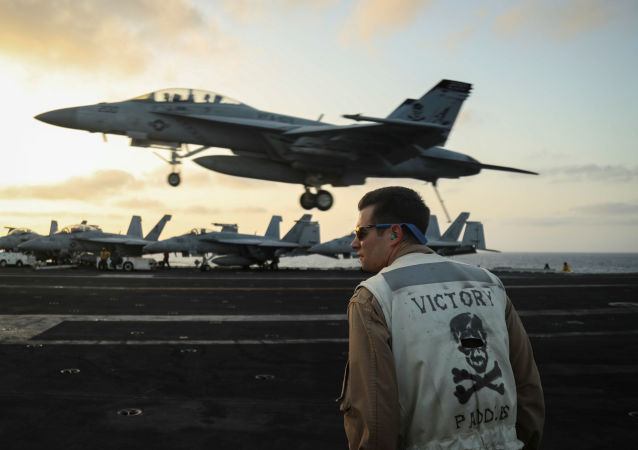A landing signals officer aboard the Nimitz-class aircraft carrier USS Abraham Lincoln (CVN 72) watches as an F/A-18F Super Hornet from the Jolly Rogers of Strike Fighter Squadron (VFA) 103 land on the flight deck of the aircraft carrier USS Abraham Lincoln (CVN 72) in the Arabian Sea, 3 June 2019. Picture taken 3 June 2019