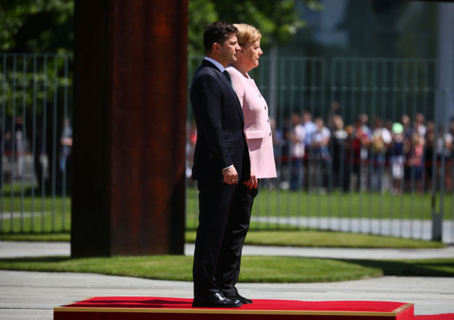 German Chancellor Angela Merkel and Ukrainian President Volodymyr Zelenskiy listen national anthems at the Chancellery in Berlin, Germany, June 18, 2019
