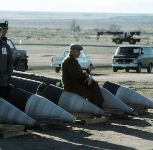 Soviet inspectors and their American escorts stand among several dismantled Pershing II missiles as they view the destruction of other missile components