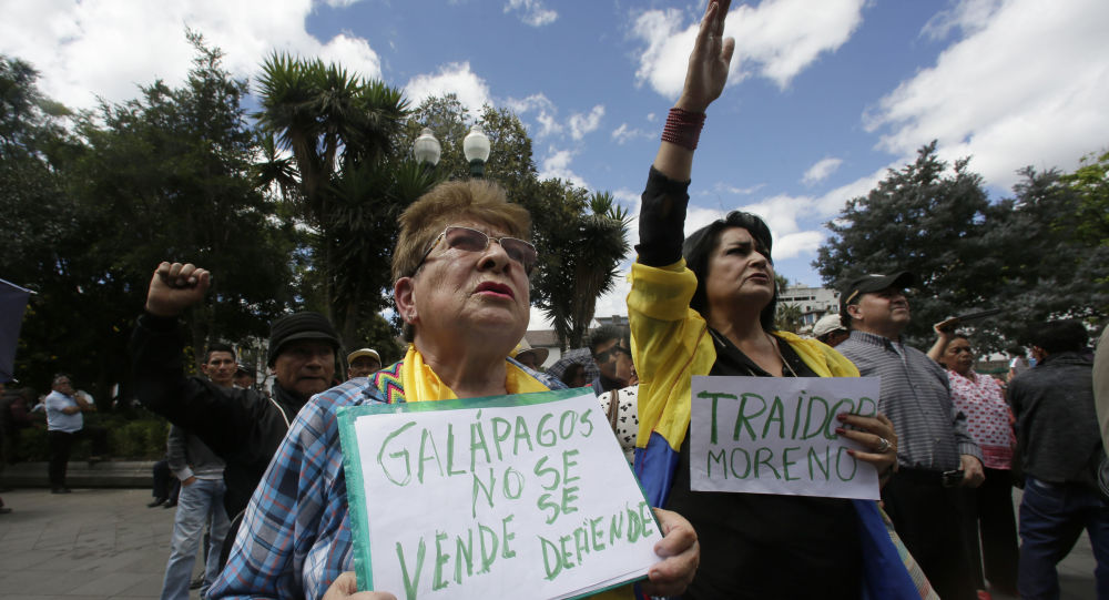 """A woman holds a sign with a message that reads in Spanish; """"Galapagos is not to be sold, but to be defended,"""" during a protest against the government's plan to allow the U.S. military to use a Galapagos island for aircraft on anti-drug trafficking flights, outside the government palace in Quito, Ecuador, Monday, June 17, 2019"""