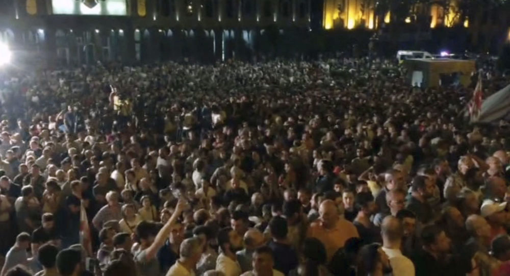 thousands of protesters gather outside the parliament building in the Georgian capital of Tbilisi