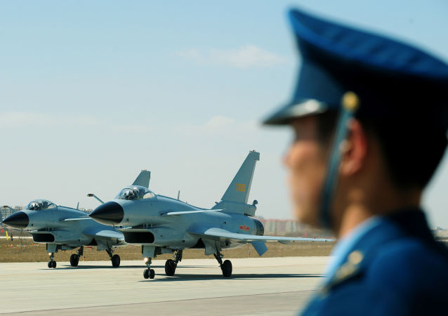 Chinese J-10 fighter jets pass an Air Force officer on the tarmac at the Yangcun Air Force base of the People's Liberation Army Air Force in Tianjin, home of the 24th Fighter Division, southeast of Beijing on 13 April 2010