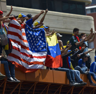 Anti-government protesters hold the US national flag next to a Venezuelan national flag during the commemoration of May Day in Caracas, on May 1, 2019 after a day of violent clashes on the streets of the capital spurred by Venezuela's opposition leader Juan Guaido's call on the military to rise up against President Nicolas Maduro