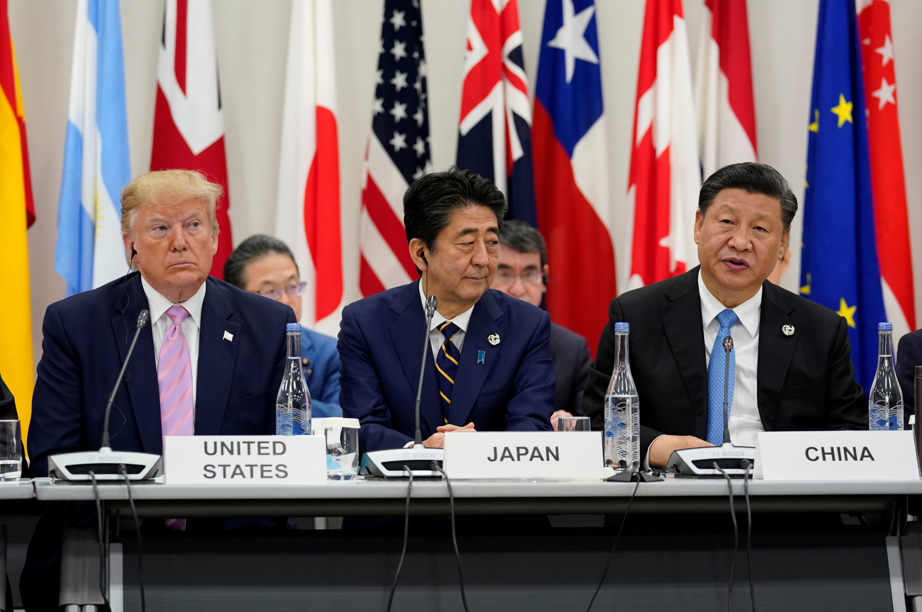 Japan's Prime Minister Shinzo Abe is flanked by U.S. President Donald Trump and China's President Xi Jinping during a meeting at the G20 leaders summit in Osaka, Japan, June 28, 2019