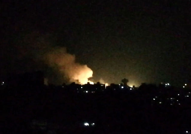 An image grab taken from an AFP video shows what appears to be smoke billowing over buildings near the Syrian capital Damascus, following a reported Israeli air strike overnight on July 1, 2019