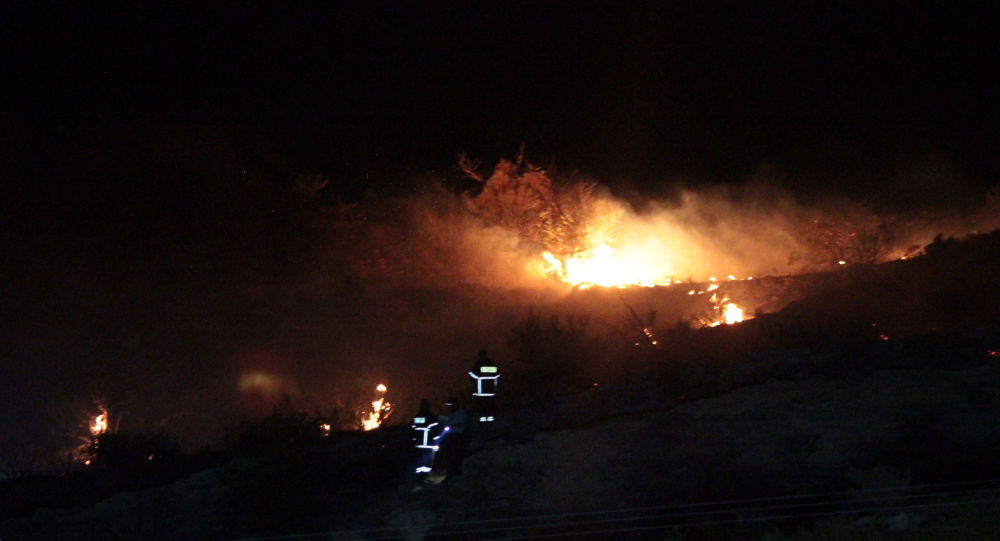 Fire is seen on a hillside where officials said was caused by a suspected Russian missile that exploded overnight on July 1, 2019, in the northern part of the divided island of Cyprus, during an Israeli aerial raid in Syria.