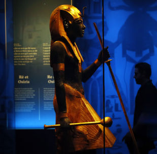 A visitor walks by a wooden guardian statue of the Ka of the king wearing the Names Headcloth displayed as part of 'Tutankhamun, the treasure of the Pharaoh', an exhibition in partnership with the Grand Egyptian Museum at the Grande Halle of La Villette in Paris, France, Thursday, March 21, 2019.