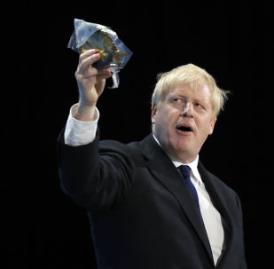 Conservative party leadership candidate Boris Johnson holds up a bagged smoked fish during his speech during a Conservative leadership hustings at ExCel Centre in London, Wednesday, July 17, 2019