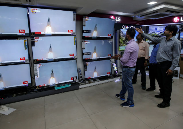 People celebrate as they watch a live broadcast of India's second lunar mission, Chandrayaan-2, inside an electronics showroom in Kolkata, India, July 22, 2019