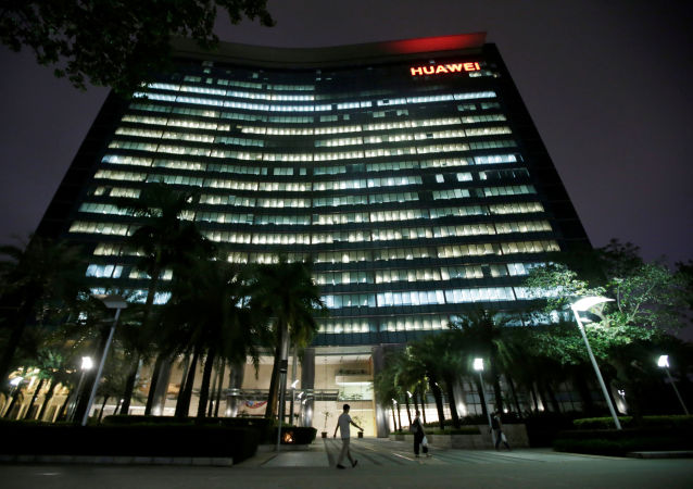 Employees walk past a research and development building with lights on at Huawei headquarters in Shenzhen