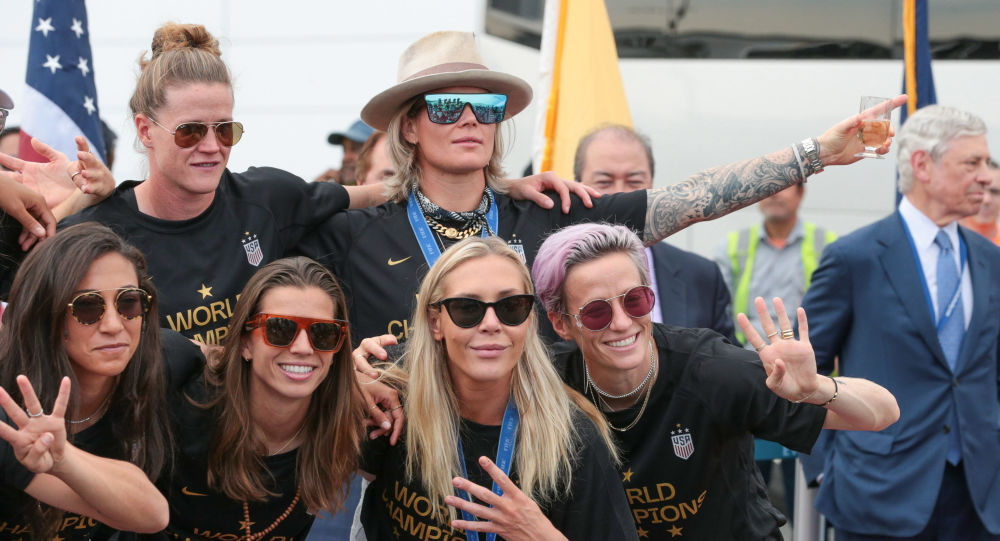 Members of the US Women's National Soccer Team pose with the trophy at Newark Liberty International Airport after winning the 2019 Women's World Cup.