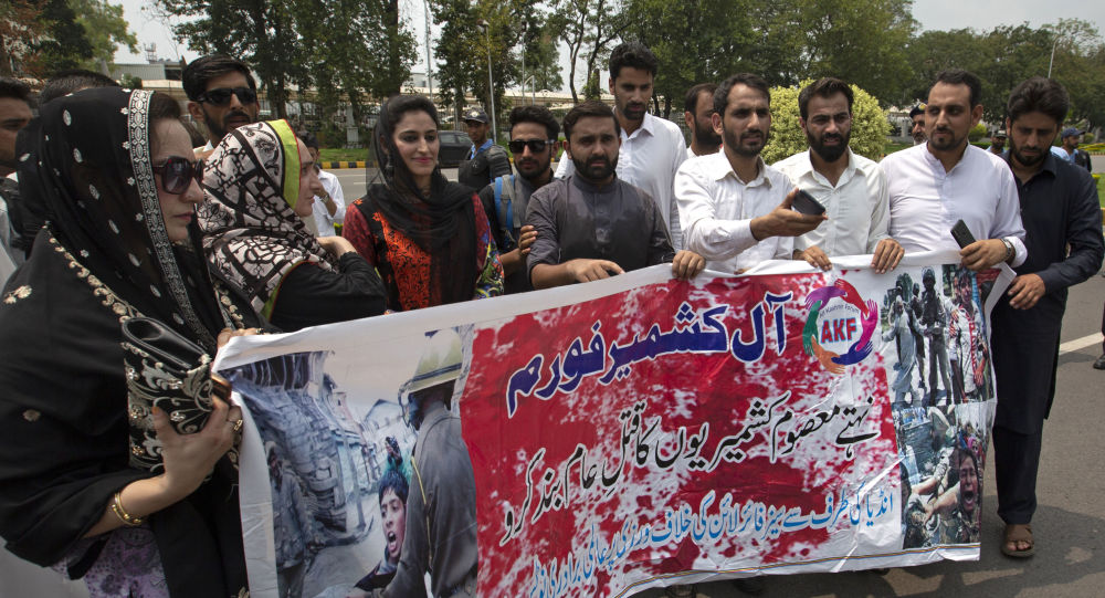 Pakistani Kashmiris protest near Indian embassy in Islamabad, Pakistan, holding banner reads stop genocide of innocent Indian Kashmiris, Monday, Aug. 5, 2019