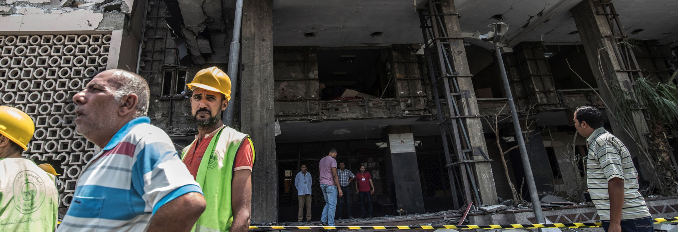Egyptians walk outside the National Cancer Institute in the capital Cairo on August 5, 2019, where an accident took place just before midnight the previous day.