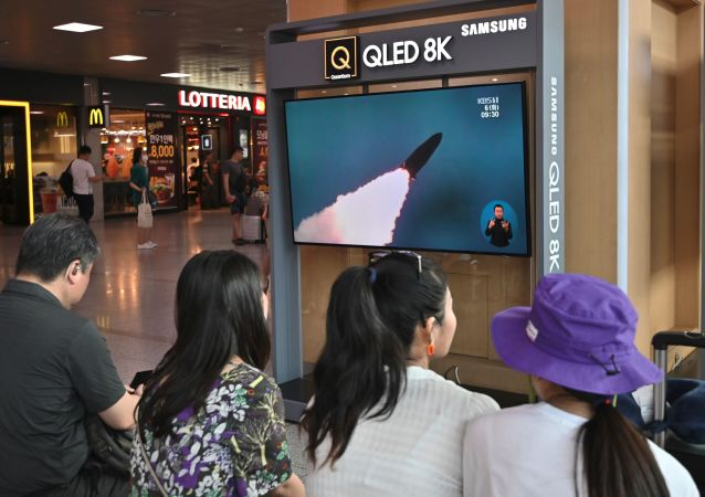 People watch a television news screen showing a file footage of North Korea's missile launch, at a railway station in Seoul on August 6, 2019.