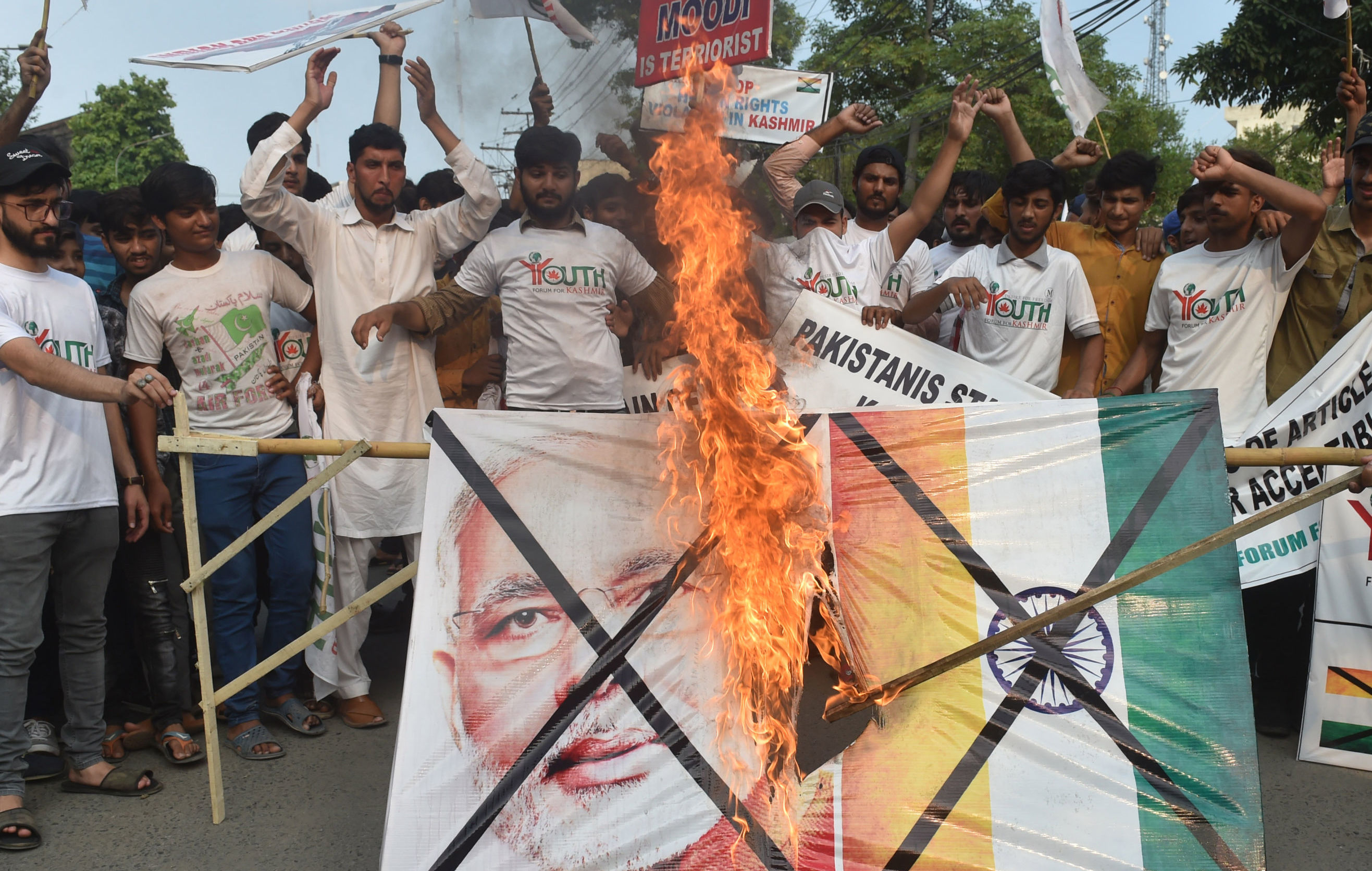 Pakistani activists of the Youth Forum for Kashmir group shout slogans as a a picture of Indian Prime Minister Narendra Modi and Indian flag is burned during a protest in Lahore on August 5, 2019, in reaction to the move by India to abolish Kashmir's special status