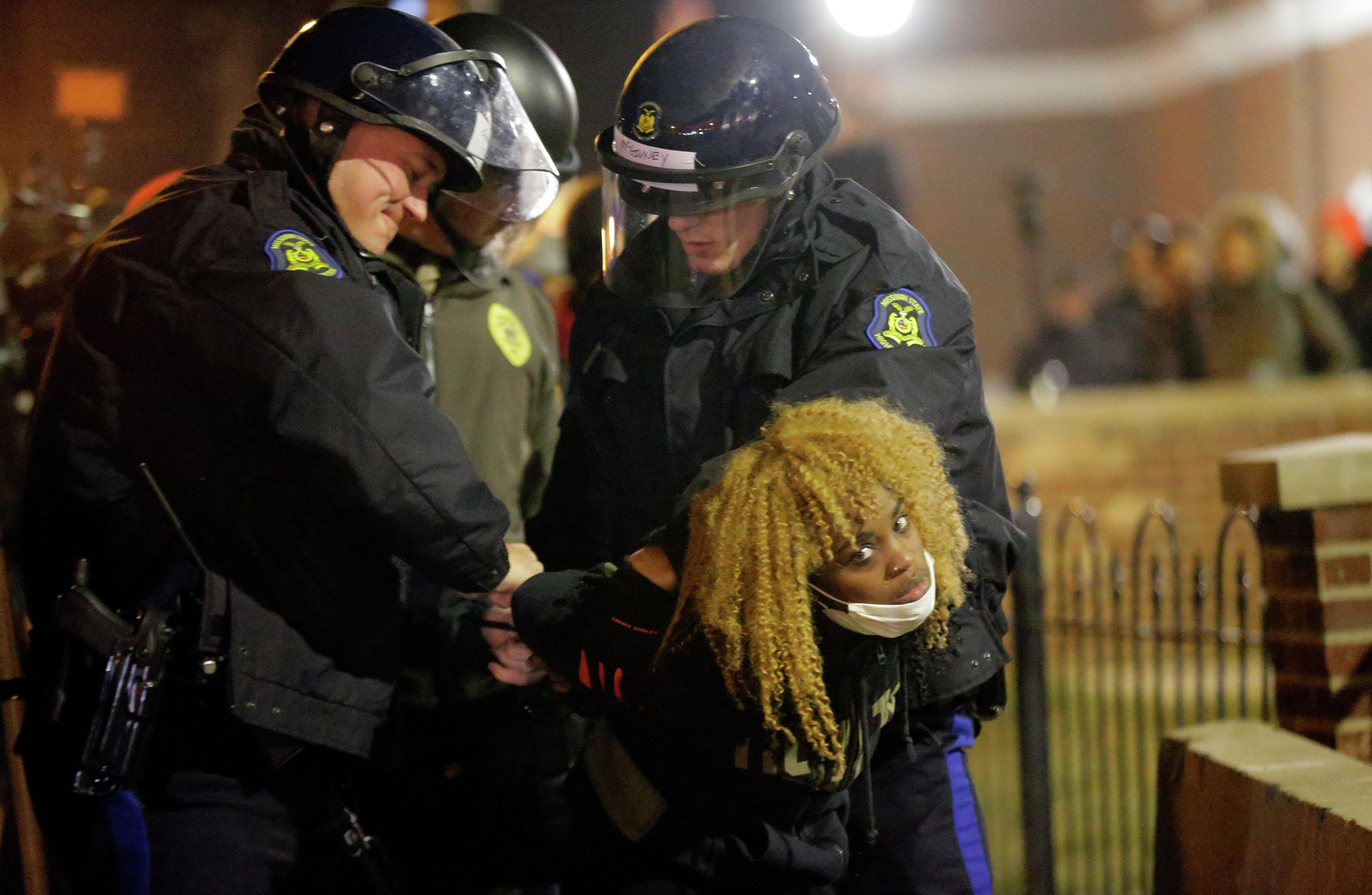 Police officers take a protester into custody Tuesday, Nov. 25, 2014, in Ferguson, Mo.