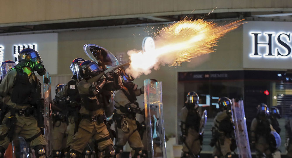 Riot police fire tear gas during the anti-extradition bill protest in Hong Kong, Sunday, Aug. 11, 2019. Police fired tear gas late Sunday afternoon to try to disperse a demonstration in Hong Kong as protesters took over streets in two parts of the Asian financial capital, blocking traffic and setting up another night of likely showdowns with riot police.