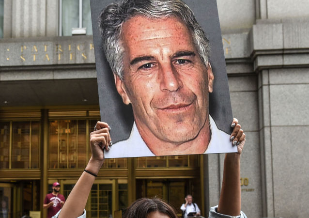(FILES) In this file photo taken on July 8, 2019, a protest group called Hot Mess hold up photos of Jeffrey Epstein in front of the Federal courthouse on July 8, 2019 in New York City