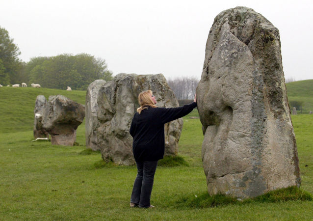 A visitor gets up close and touch one of the stones that form the largest stone circle in Europe at Avebury, Wiltshire