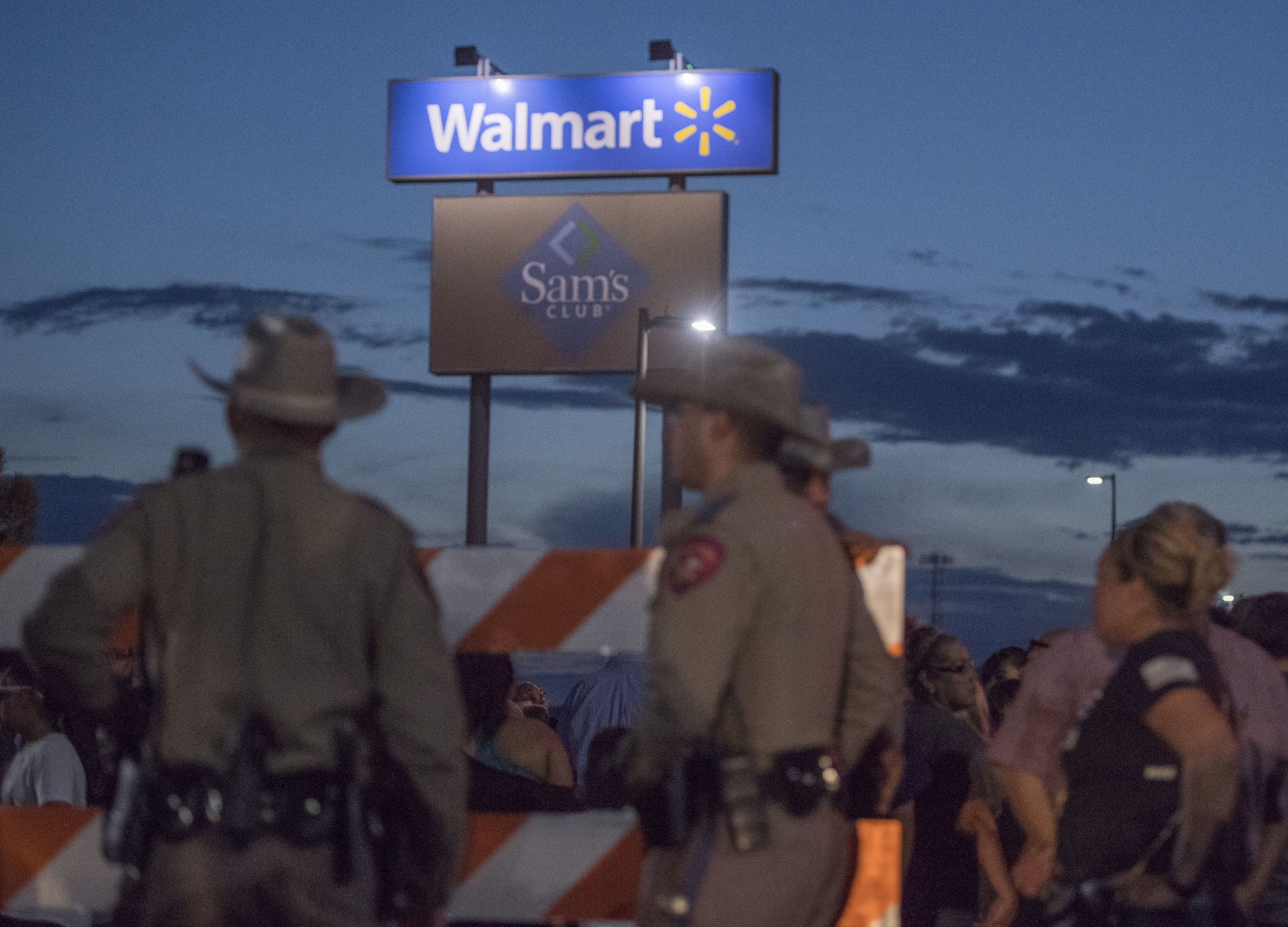 Texas State Troopers keep watch at the makeshift memorial for victims of the shooting that left a total of 22 people dead at the Cielo Vista Mall WalMart in El Paso, Texas, on August 6, 2019