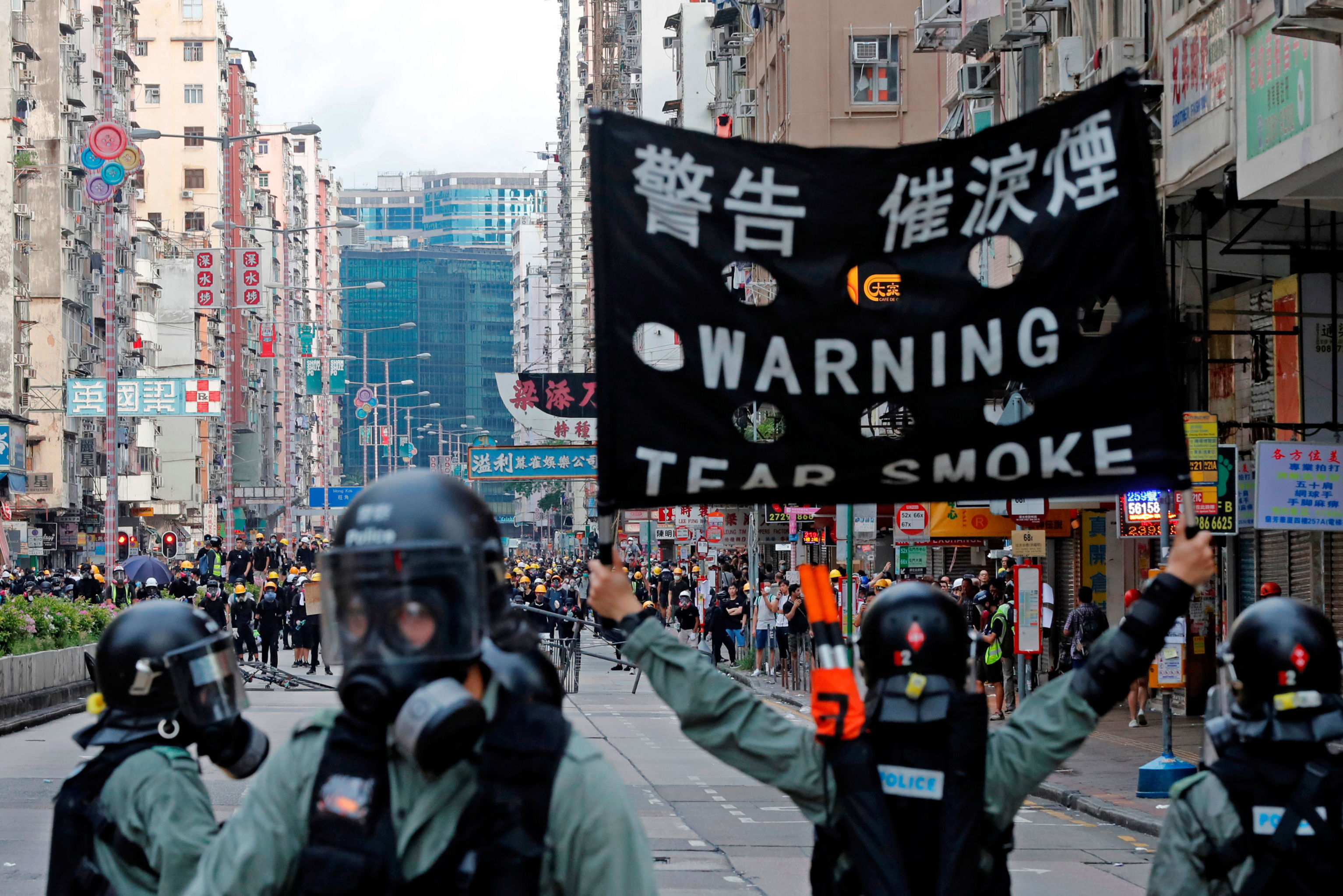 A riot police raises a warning flag as they try to disperse anti-extradition bill protesters by tear gas at Sham Shui Po in Hong Kong, China August 11, 2019. REUTERS/Tyrone Siu