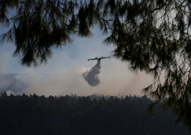 A firefighting plane makes a water drop as a wildfire burns near the village of Stavros on the island of Evia, Greece