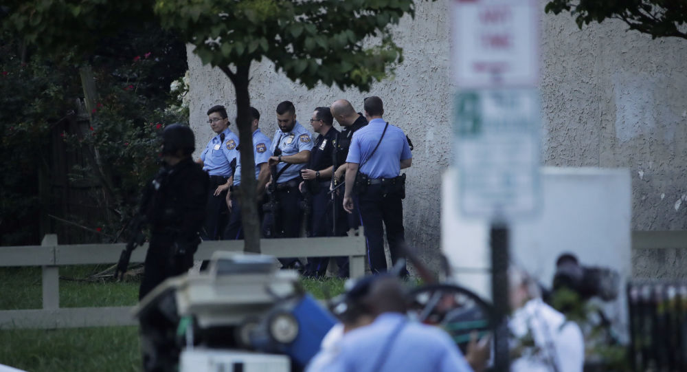 Police officers stand near the scene of a shooting Wednesday, Aug. 14, 2019, in the Nicetown neighborhood of Philadelphia.