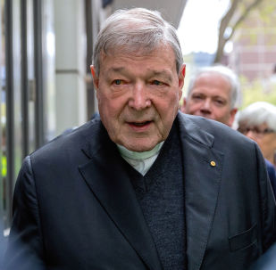 Vatican Treasurer Cardinal George Pell is surrounded by Australian police as he leaves the Melbourne Magistrates Court in Australia