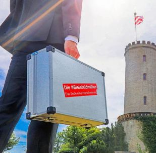 A man is holding a suitcase with 'the Bielefeld million' sticker against the backdrop of Sparrenburg Castle, a favourite tourist destination in Bielefeld.