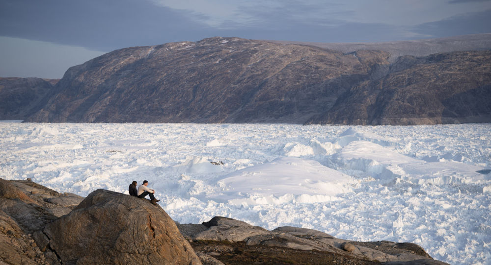 In this 16 August 2019, photo, New York University student researchers sit on a rock overlooking the Helheim glacier in Greenland.