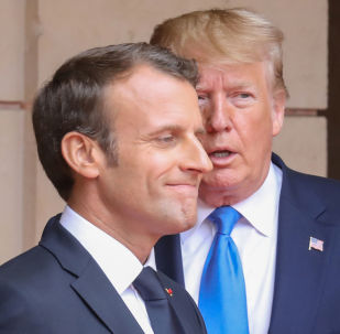 FILE PHOTO: French President Emmanuel Macron speaks with US President Donald Trump on the sidelines of commemorations marking the 75th anniversary of the World War II D-Day landings in Normandy, France,  6 June 2019