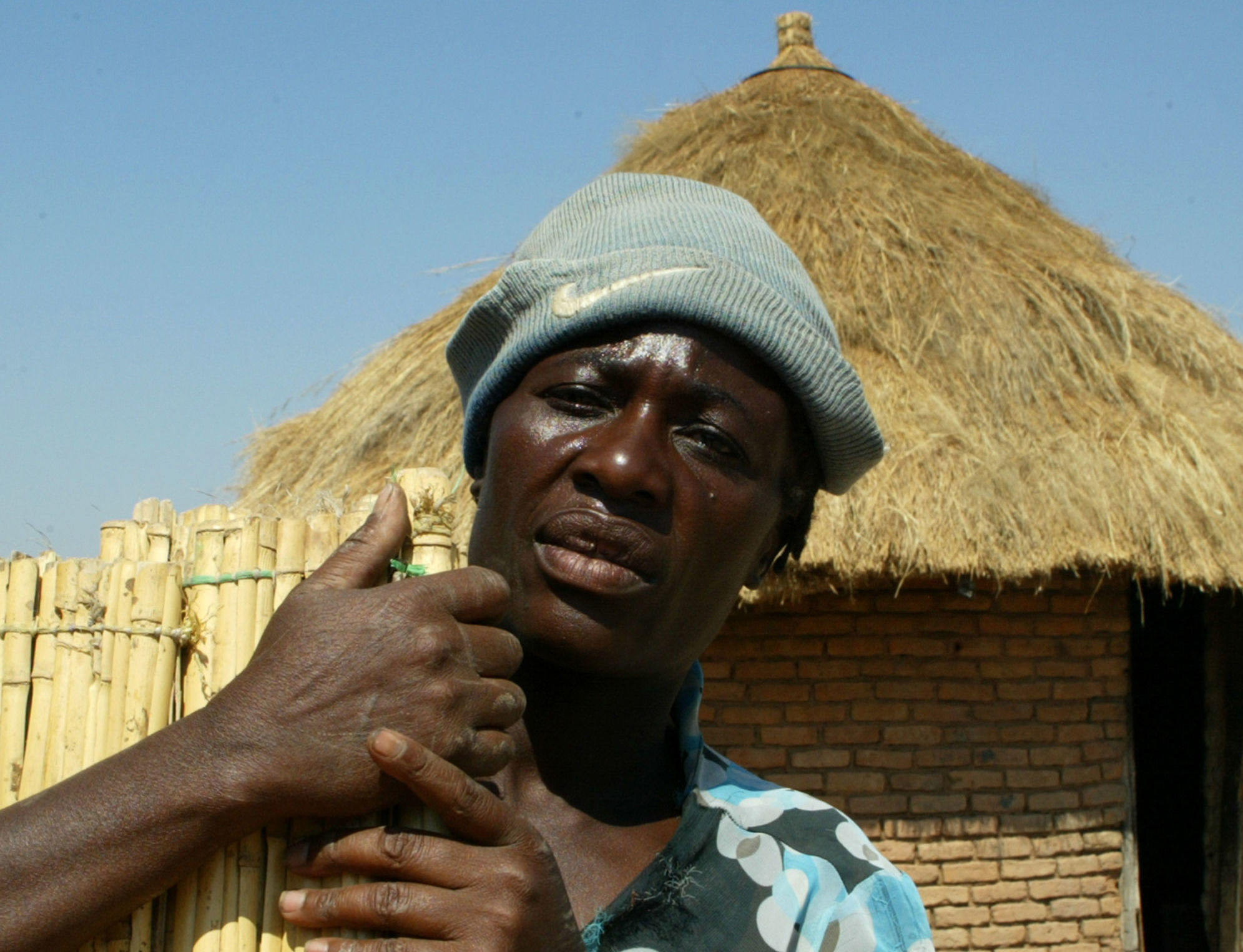 Zimbabwean villager Connie Garandemo poses in front of a hut on August 6, 2012 in Zimbabwe's Buhera district
