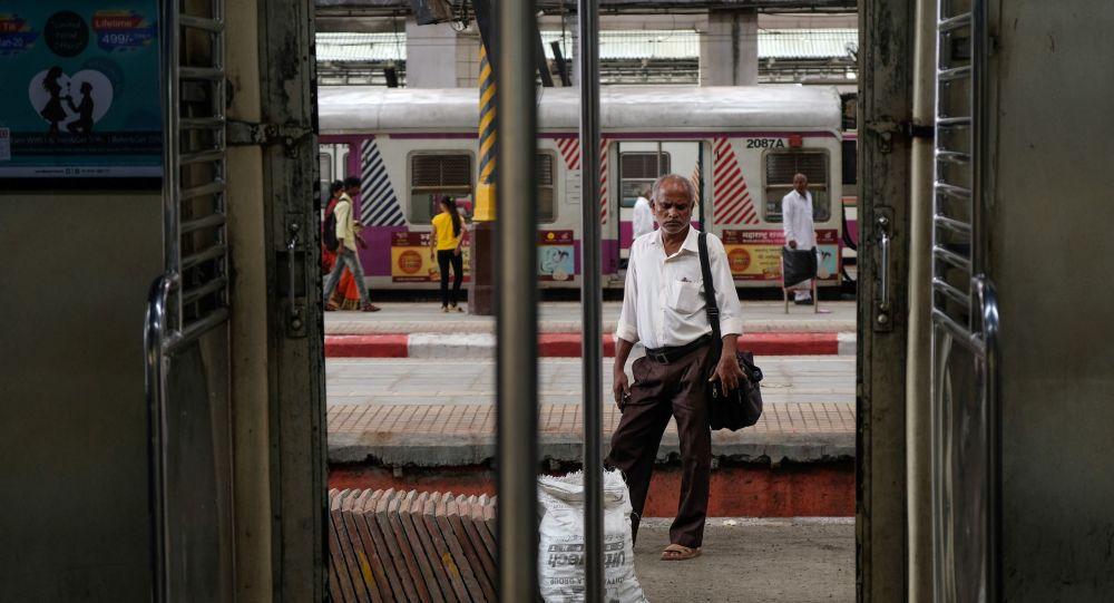 A man waits for a train at a railway station in Mumbai.