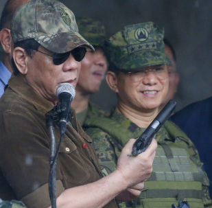 President Rodrigo Duterte holds a pistol as he addresses the troops as he declared the liberation of Marawi city in the southern Philippines after almost five months of a siege by pro-Islamic State group militants Tuesday, Oct. 17, 2017