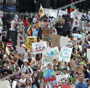 Protesters take over Dearborn Street in Chicago's famed Loop during a global climate change march Friday, Sept. 20, 2019, in Chicago. Throughout the world Friday, young people banded together to demand that world leaders headed to a United Nations summit in New York step up their efforts to combat climate change.  (AP Photo/Charles Rex Arbogast)