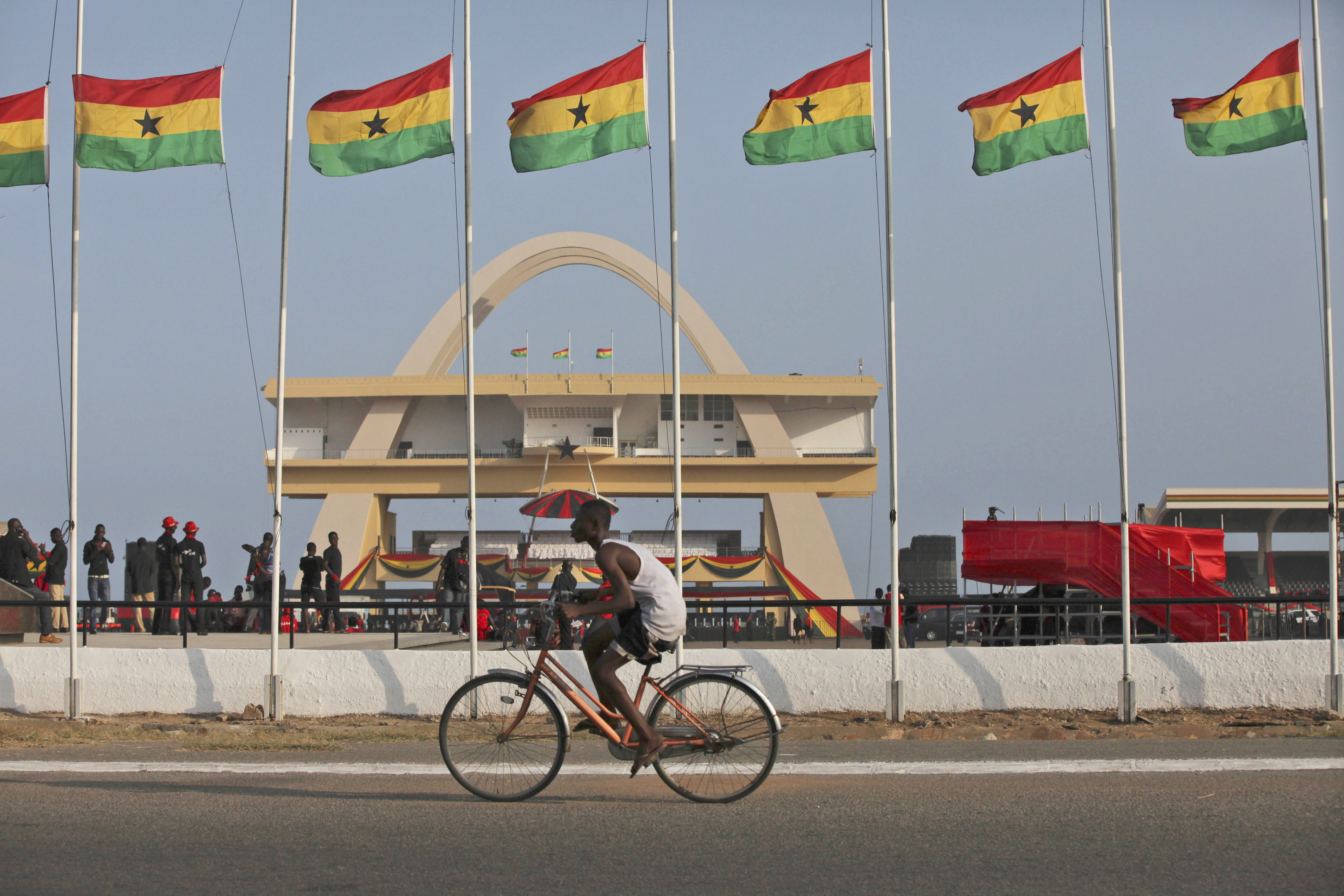 A man rides a bicycle past Ghanian flags flown at half mast to honor late Ghanian President, John Evans Atta Mills at the independence square in Accra, Ghana, Thursday, Aug.9, 2012.