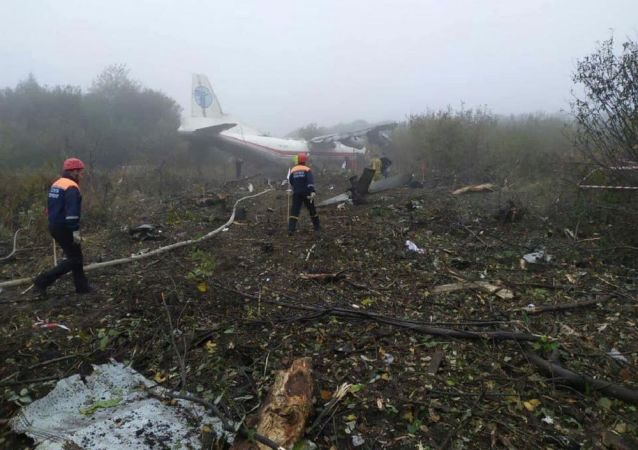 Members of emergency services work at the site of the Antonov-12 cargo airplane emergency landing in Lviv region, Ukraine October 4, 2019