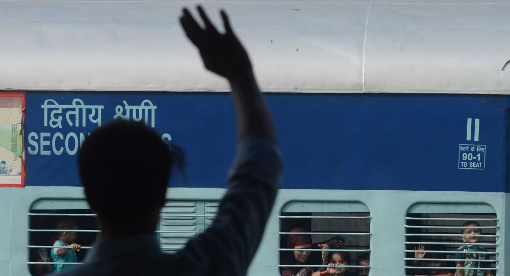 A Pakistani man waves to his Indian Muslim relatives on their departure to India via the Samjhota Express train, also called the Friendship Express that runs between Delhi and Attari in India and Lahore in Pakistan, at the railway station in Lahore on August 8, 2019.