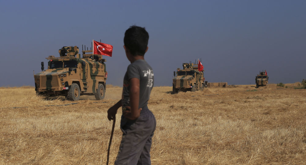 Turkish armoured vehicles patrol as they conduct a joint ground patrol with American forces in the so-called safe zone on the Syrian side of the border with Turkey, near the town of Tal Abyad, northeastern Syria, Friday, Oct. 4, 2019