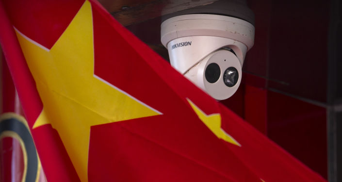 A Chinese flag hangs near a Hikvision security camera outside of a shop in Beijing, Tuesday, Oct. 8, 2019