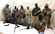 Hooded and clad in military fatigues, armed with guns, rocket launchers, members of a commando claiming to belong to the National Liberation Front of Corsica answer media questions at a press conference held near Ajaccio on May,2010