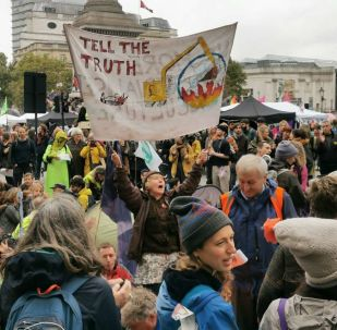 An activist holds a banner on climate change as protestors stage a sit in at a major road at Trafalgar Square in London, UK