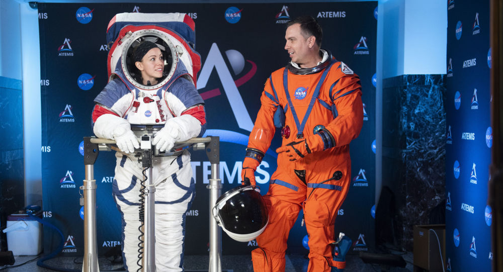 The two NASA spacesuit prototypes for lunar exploration, one for launch and re-entry aboard the agency's Orion spacecraft, known as the Orion Crew Survival Suit, is worn by Dustin Gohmert, right, and one for exploring the surface of the Moon's South Pole, known as the Exploration Extravehicular Mobility Unit (xEMU) is worn by Kristine Dans on Tuesday, Oct. 15, 2019, at NASA Headquarters in Washington