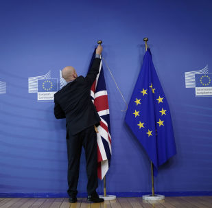 An official hangs a Union Jack next to an European Union flag at EU Headquarters in Brussels on October 17, 2019, ahead of a European Union Summit on Brexit.