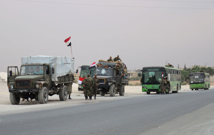 A convoy of military vehicles and  transporting Syrian regime troops are stationed on the outskirts of the northern Syrian border town of Kobane (also known as Ain Arab) on October 16, 2019
