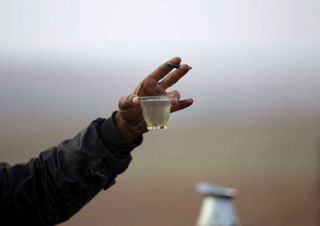 A worker shows off the final fuel product at a makeshift oil refinery site in Marchmarin town, southern countryside of Idlib, Syria December 16, 2015.