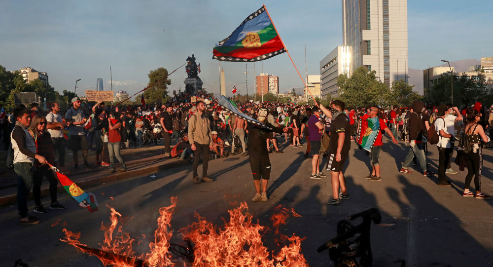 Demonstrators wave a Mapuche flag during a protest against Chile's state economic model in Santiago, Chile October 26, 2019